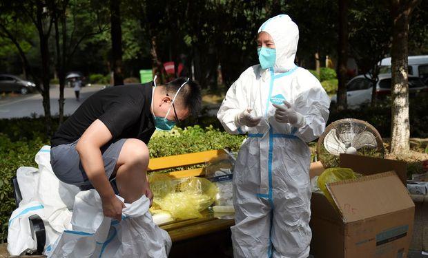 Un trabajador médico se pone un traje protector en medio de una prueba masiva por coronavirus en Wuhan, provincia de Hubei, China, el 4 de agosto de 2021. REUTERS / Stringer