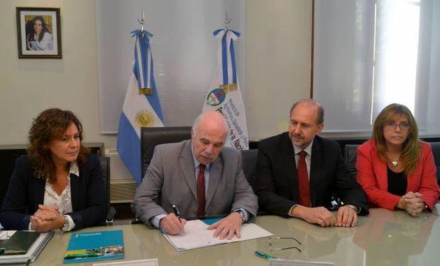 Casamiquela al firmar el decreto junto a funcionarios del Ministerio, Perotti y Giaccone.