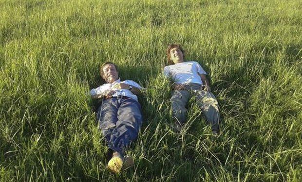 Padre e hijo sobre un colchón de pasto.