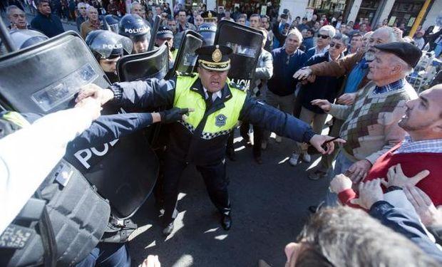 Un jefe de la Policía separa a sus subordinados y a los productores con sus brazos, en uno de los momentos tensos de la protesta del campo.